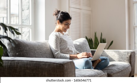 Smiling indian millennial girl sit relax on couch using modern laptop browsing unlimited wireless internet, happy young woman freelancer work on computer typing texting from home, technology concept