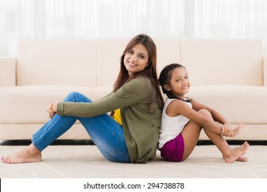 Smiling Indian mother and daughter sitting on the floor back to back