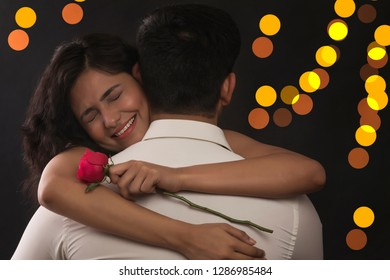 Smiling Indian woman hugging her boyfriend and holding the rose she got for Valentine's Day