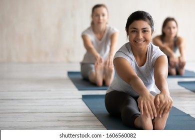 Smiling Indian woman practicing yoga at group lesson, doing Seated forward bend exercise, looking at camera, diverse people stretching in paschimottanasana pose on mats, portrait with copy space
