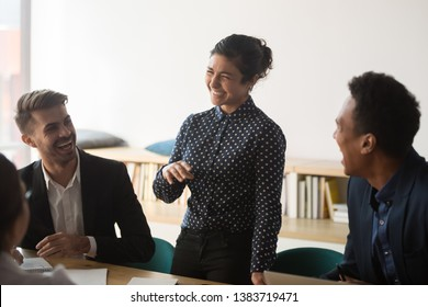 Smiling indian woman stand talking on meeting with multiracial colleagues, laugh discussing ideas, happy multiethnic employees joke having fun brainstorming briefing in conference room