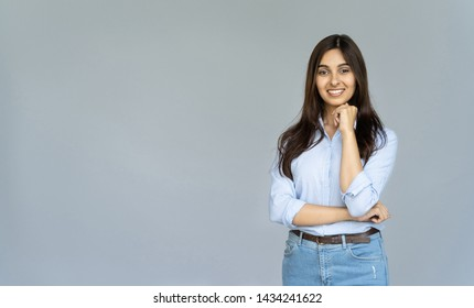 Smiling indian young business woman wear blue jeans shirt looking at camera isolated on grey blank studio background with copy space, happy pretty hindu female student posing on gray wall, portrait