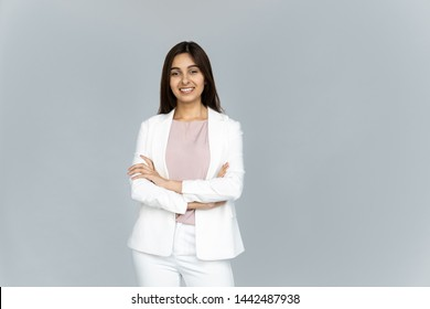 Smiling indian young businesswoman wear white suit looking at camera isolated on grey studio background, happy attractive confident hindu business lady professional with arms crossed portrait
