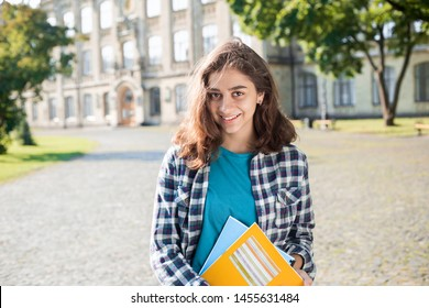 Smiling Indian young female student holds educational books standing against the background of college. Happy brunette girl near the university.