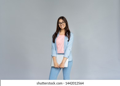 Smiling indian young woman college university school student wear glasses holding laptop computer isolated on grey studio background, happy teen girl looking at camera stand with device, portrait