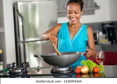 Smiling Indonesian woman stirring food in wok in kitchen