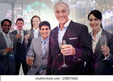 Smiling inernational business team holding glasses of Chamoagne against colourful fireworks exploding on black background