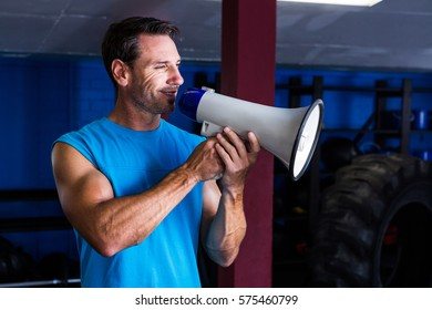 Smiling instructor holding megaphone in gym