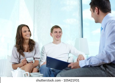 Smiling insurance agent making a business proposition to a lovely couple