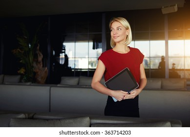 Smiling intelligent female restaurant owner waiting for a clients while holding touch pad with copy space screen, woman in good mood looking away while standing with digital tablet in modern interior