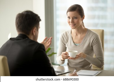 Smiling interested businesswoman listening to businessman talking during coffee break, enjoying pleasant conversation with partner, discussing great business idea, new opportunity while drinking tea