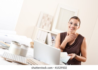 Smiling interior designer with color swatch and paint at office