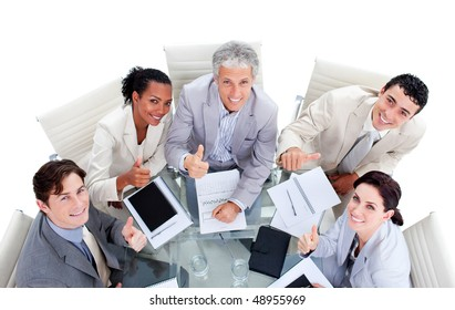 Smiling international business people with thumbs up in a meeting