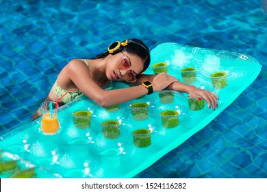 Smiling interracial brunette posing in a reclining pool on a cocktail mattress, wearing yellow headphones and a wristwatch in yellow-pink gradient sunglasses, a green bikini. Enjoyment.
