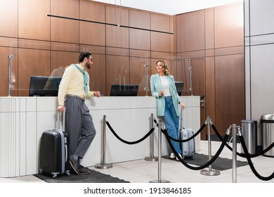 Smiling interracial couple with suitcases waiting near hotel reception