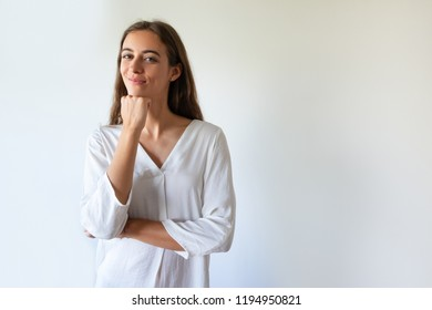 Smiling introspective girl leaning head on hand and looking at camera. Content confident young woman in white blouse standing against isolated background. Young entrepreneur concept