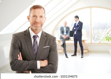 Smiling investment advisor businessman standng with folded arms at the office after business meeting. Unrecognizable business people standing at the background.