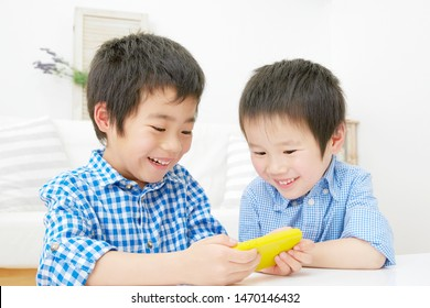 smiling Japanese children with smart phone