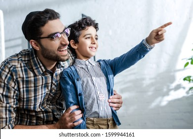 smiling jewish son pointing with finger and looking through window with father in apartment