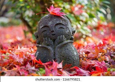 Smiling Jizo statue with autumn leaves in the garden of Enko-ji template in Kyoto, Japan
