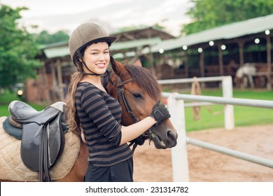 Smiling jockey girl stroking her horse