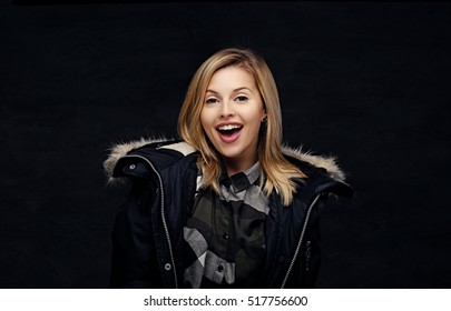 Smiling joyful blonde female in a winter warm jacket with fur hood.