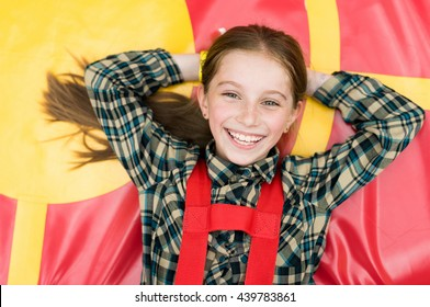 smiling joyful girl lying on colorful trampoline in entertainment center