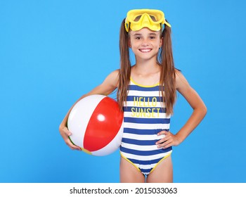 Smiling joyful girl in striped swimsuit and yellow goggles on head holding inflatable ball under her arm, isolated on blue studio background. Concept of childrens recreation at sea and summer holidays