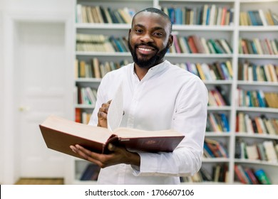 Smiling joyful male african american university student standing in modern reading hall of college library, holding open book and looking at camera. Education concept, book day, knowledge