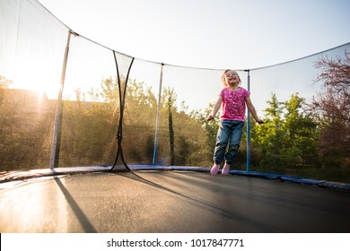 Smiling kid in the backyard bouncing on trampoline