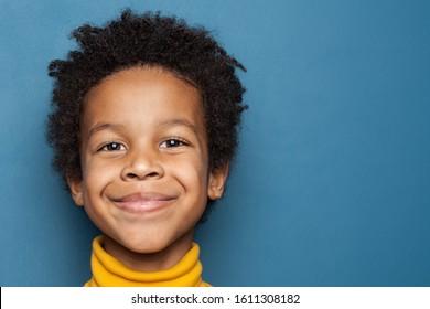 Smiling kid boy portrait. Little african american child boy on blue background