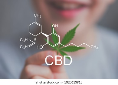Smiling kid child holding a hemp leaf. Concepts of using marihuna for medicinal purposes for children, Medical use of non-psychoactive cannabidiol CBD medical