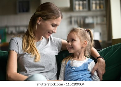 Smiling kid daughter looking at loving single mother hugging her on sofa, young woman mommy embracing cute happy girl showing care and support, sincere warm relationships of mom and child concept