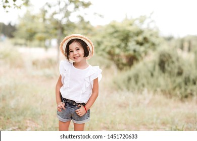 Smiling kid girl 3-4 year old wearing summer clothes and hat posing in meadow. Looking at camera. Summer season.