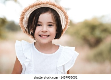 Smiling kid girl 3-4 year old wearing straw hat and white stylish shirt outdoors. Looking at camera.