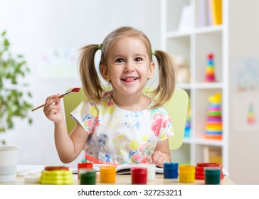 smiling kid girl painting with paintbrush at home or day care center