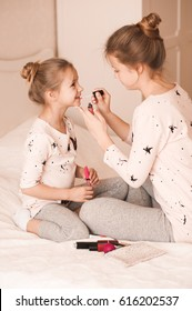 Smiling kid girl playing with cosmetics in room. Childhood.