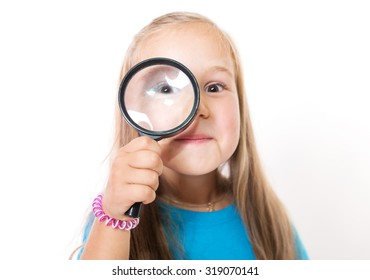 Smiling kid looking through a magnifying glass