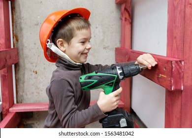 Smiling kid in orange helmet drives screw into wooden plank by electric screwdriver