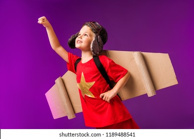 smiling kid with plane wings and goggles standing with outstretched arm to fly isolated on purple