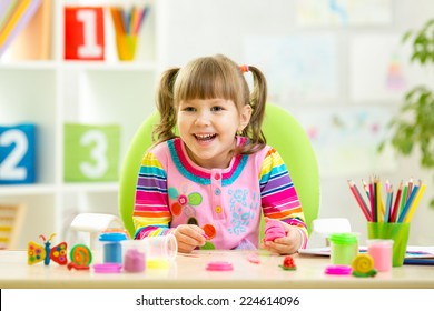 smiling kid playing with colorful clay at home