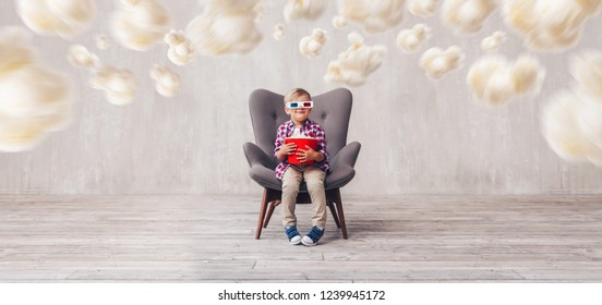 Smiling kid with popcorn in 3d glasses in the cinema