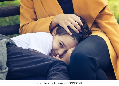 Smiling kid relaxing on mothers lap. Shy boy feeling safe in mother's lap.