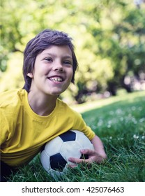 Smiling Kid With Soccer Ball on Grass Field