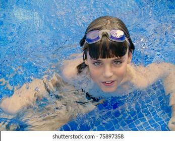 smiling kid swim in a blue pool