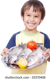 Smiling kid with three fresh fishes on table