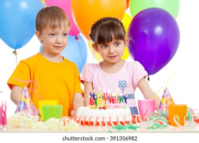 Smiling kids with birthday cake and color ballons