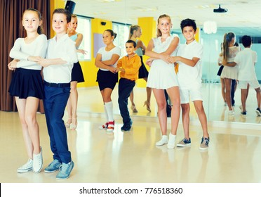 Smiling kids are dancing tango in class.