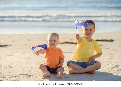 Smiling kids with flags of Australia at the beach