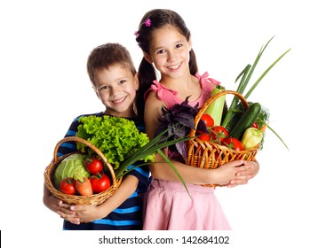 Smiling kids with fresh vegetables in baskets, isolated on white